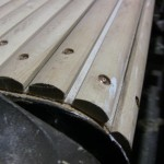 Close-up showing slats with rivets going through the canvas and into the fabric belts under the canvas (